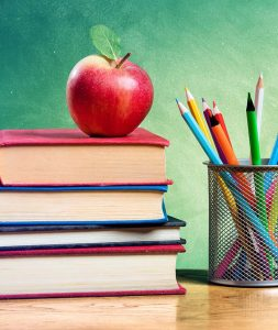 A stack of books with an apple on top and colored pencils to the right of that in a wire basket