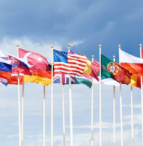Flags of different countries on high flagpoles. USA flag in the middle.
